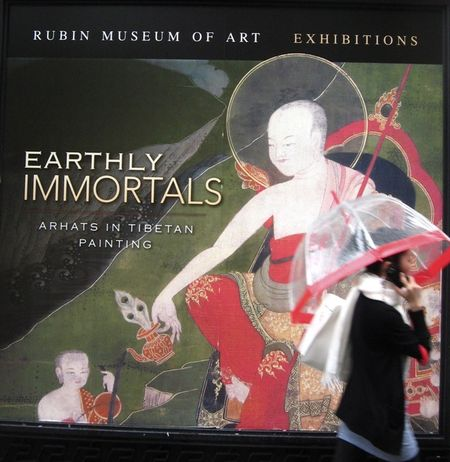 Rubin Museum Of Art, Earthly Immortals, Arhats in Tibetan painting, poster, woman with umbrella in front of tibetan poster, umbrella red stripe, red stripe as halo